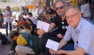 Integrantes del Movimiento 15-M muestran dos sobres electorales en la concentración de la plaza de la Constitución de Huelva. (J. C.)