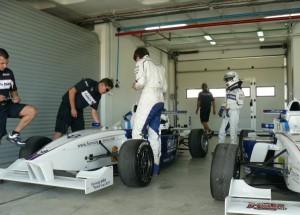 Pilotos ante sus coches en el circuito de Monteblanco.