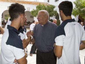 Varios jugadores del Recre conversan con el sacerdote Antonio Bueno tras el acto de la ofrenda floral a la Virgen de la Cinta. (Julián Pérez)