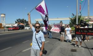 Uno de los asistentes a la protesta ondea la bandera del Motoclub de Faro. (H. C.)