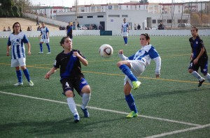 Jugadoras del Sporting y el Rayo Vallecano peleando por un balón.