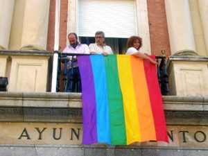 Responsables municipales de IU cuelgan la bandera arcoiris.