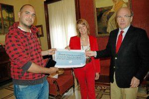 Pedro Rodríguez entre el premio a Adrián Infante, ganador del certamen, en presencia de Pilar Miranda.