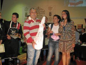 El padre de la ganadora del Guarro bocón recoge uno de los jamones del lote que les ha tocado gracias a este concurso.