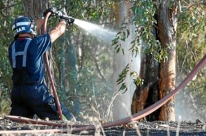 Un bombero refresca la zona incendiada.
