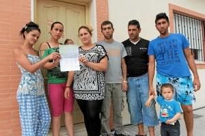 'Okupas' de la calle Huelva de Bollullos muestran las firmas que han recogido para que les den una solución. (José Carlos Sánchez / Multimagenestudio)