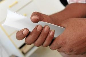 Una de las personas que ocupa una vivienda en Bollulos mantienen en sus manos documentos relativos a su situación. (José Carlos Sánchez / Multimagenestudio)