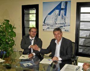 El director de Cáritas y el gerente de Aguas de Huelva estrechan la mano tras rubricar el acuerdo.