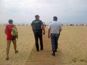Efectivos de las fuerzas de seguridad patrullan por una playa.