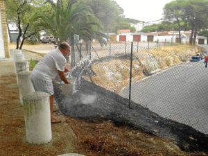 Un vecino refresca la zona con un cubo de agua. (José Carlos Sánchez-Multimagenestudio)