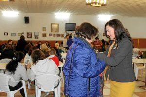 La concejala pone un lazo blanco a una de las participantes