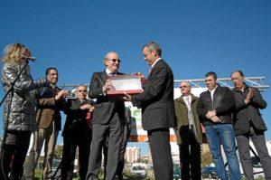 El alcalde recibe la placa homenaje.