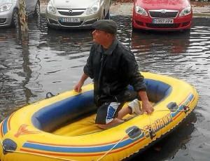 Un hombre en una barca hinchable por las calles de Isla Cristina. (Foto: Huelvaya)