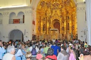 Interior de la ermita, con cientos de personas rezándole a la Virgen.