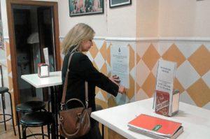 La alcaldesa pega el bando en un lugar público para su conocimiento.