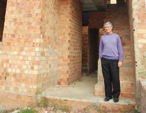 Juan Maestre junto a la casa paralizada por problemas desde 2003.