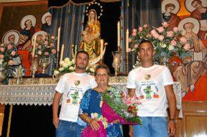 La alcaldesa, junto a dos jugadores, entrega el ramo a la Virgen